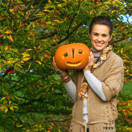 Trick or Treat. happy young woman on Halloween at the park showing pumpkin Jack OLantern