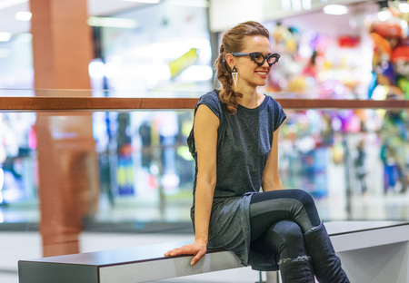 Trick or Treat. Portrait of smiling young woman in bat eyeglasses on Halloween at the mall looking into the distance while sitting on a bench Stock Photo