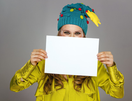 Stunning season. elegant woman in funny Christmas hat isolated on grey background showing at blank paper Stock Photo