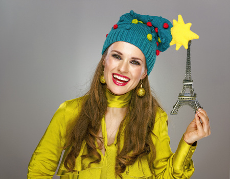 Stunning season. smiling elegant woman in funny Christmas hat isolated on grey background holding Eiffel Tower Stock Photo
