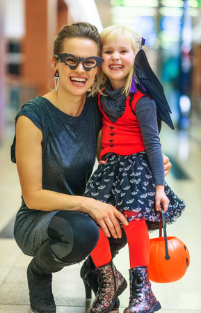 Trick or Treat. Portrait of happy modern mother and child in bat costumes on Halloween at the mall
