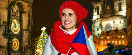 Magie auf den Straßen der Altstadt zu Weihnachten. lächelnde junge touristische Frau im roten Hut und Schal am Weihnachten auf altem Marktplatz in Prag Czechia mit der tschechischen Markierungsfahne, die in den Abstand schaut Standard-Bild - 86899754