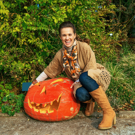 Trick or Treat. happy young woman on Halloween outdoors showing huge pumpkin Jack O'Lantern