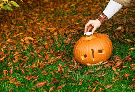 Trick or Treat. Closeup on young woman on Halloween at the park putting candle in carved Halloween pumpkin Jack O'Lantern