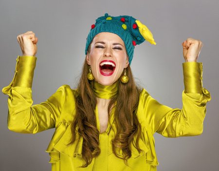 근사한 시즌. 회색 배경에 고립 된 재미있는 크리스마스 모자에 행복 한 현대 여자 기쁨