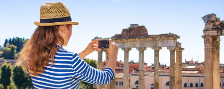Roman Holiday. modern tourist woman in the front of Roman Forum in Rome, Italy with digital camera taking photo