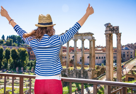 Roman Holiday. Seen from behind young tourist woman near Roman Forum in Rome, Italy rejoicing