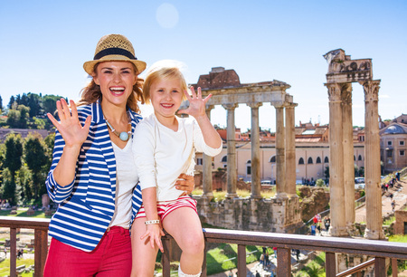 Roman Holiday. smiling modern mother and child tourists near Roman Forum in Rome, Italy handwaving Stok Fotoğraf