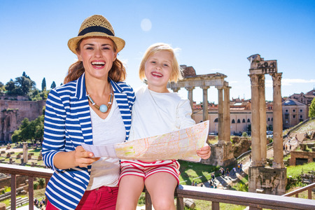 Roman Holiday. smiling young mother and daughter travellers in the front of Roman Forum in Rome, Italy with map 版權商用圖片