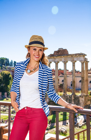 Roman Holiday. Portrait of smiling trendy woman against Roman Forum in Rome, Italy looking into the distance