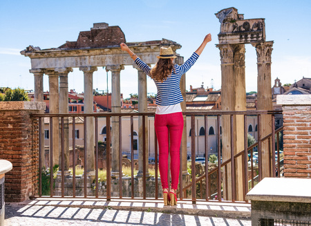 Roman Holiday. Seen from behind trendy tourist woman in the front of Roman Forum in Rome, Italy rejoicing