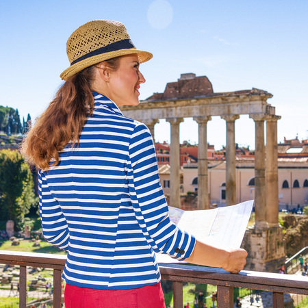 Roman Holiday. Seen from behind elegant woman against Roman Forum in Rome, Italy with map