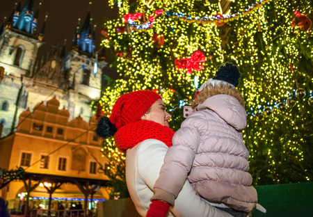 Magic on streets of the old town at Christmas. Seen from behind young mother and daughter travellers at Christmas in Prague Czech Republic