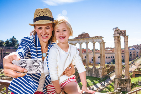 Roman Holiday. smiling modern mother and child tourists against Roman Forum in Rome, Italy with phone taking selfie