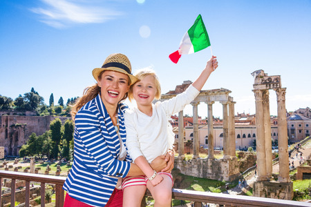 Roman Holiday. smiling modern mother and child tourists in the front of Roman Forum in Rome, Italy rising Italian flag