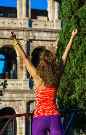 Gladiator inspiring trainings. Seen from behind modern sportswoman in sports gear near Colosseum in Rome, Italy rejoicing