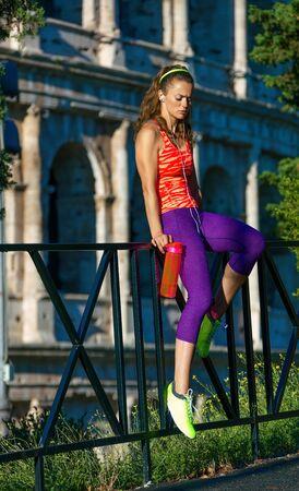 mujer deportista: Entrenamientos inspiradores de Gladiador. deportista elegante en ropa deportiva cerca del Coliseo en Roma, Italia con botella de agua sentado