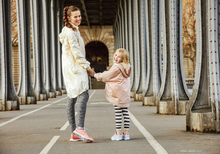 Year round fit & hip in Paris. Full length portrait of happy active mother and child in sport style clothes on Pont de Bir-Hakeim bridge in Paris