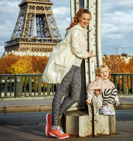 Year round fit & hip in Paris. Full length portrait of smiling healthy mother and daughter in sport style clothes on Pont de Bir-Hakeim bridge in Paris