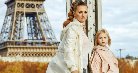 Year round fit & hip in Paris. Full length portrait of healthy mother and child in sport style clothes standing on Pont de Bir-Hakeim bridge in Paris Stock Photo