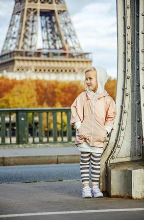 파리에서 1 년 내내 적합 & 엉덩이. 파리에서 퐁 드 Bir-Hakeim 다리에 스포츠 스타일 옷에서 웃는 활성 아이의 미소의 전체 길이 초상화 제쳐두고보고