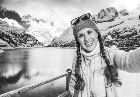 blackwhite: Winter on higher level of fun. smiling young woman in Alto Adige, Italy taking selfie Stock Photo