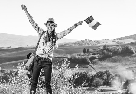 Discovering magical views of Tuscany. smiling young woman hiker in hat with bag on Tuscany hike with Italian flag