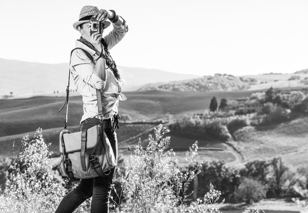 Discovering magical views of Tuscany. active woman hiker with bag on Tuscany hike taking photo with vintage photo camera