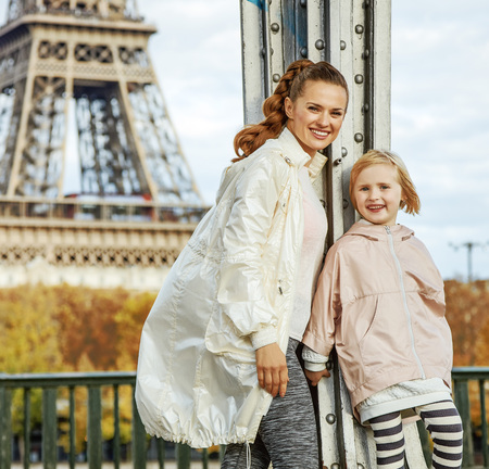Year round fit & hip in Paris. Portrait of happy active mother and daughter in sport style clothes on Pont de Bir-Hakeim bridge in Paris Stock Photo