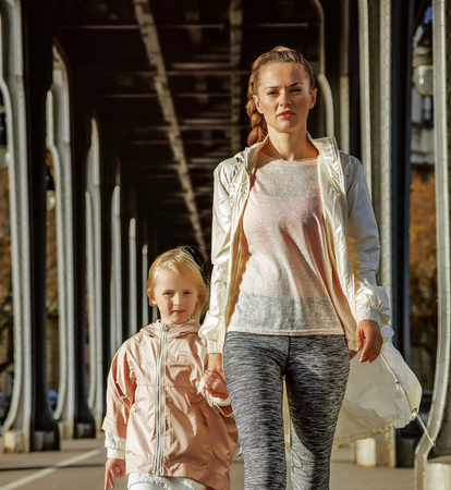 Year round fit & hip in Paris. Full length portrait of active mother and child in sport style clothes on Pont de Bir-Hakeim bridge in Paris going forward Stock Photo