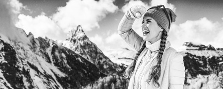 Winter on higher level of fun. happy young woman in the front of mountain landscape in Alto Adige, Italy looking into the distance