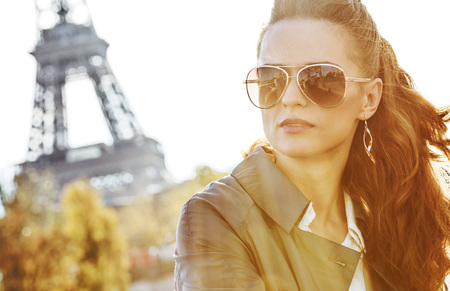 Autumn getaways in Paris. young elegant woman in sunglasses on embankment near Eiffel tower in Paris, France looking into the distance 版權商用圖片
