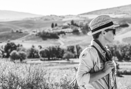 Discovering magical views of Tuscany. adventure woman hiker with bag hiking in Tuscany looking into the distance