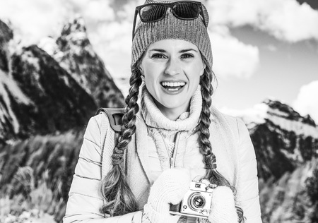Winter on higher level of fun. Portrait of smiling elegant tourist woman against mountain landscape in South Tyrol, Italy with retro photo camera