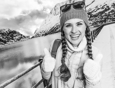 Winter on higher level of fun. happy modern traveller woman against mountain landscape with lake in South Tyrol, Italy showing thumbs up Stock Photo