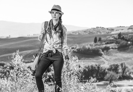 Discovering magical views of Tuscany. active woman hiker with bag on Tuscany hike looking into the distance