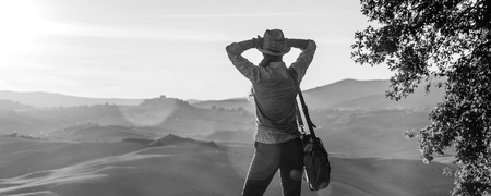 Discovering magical views of Tuscany. Seen from behind relaxed adventure woman hiker in hat with bag enjoying sunset in Tuscany Imagens
