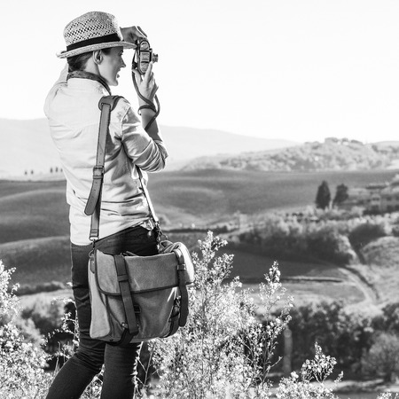 Discovering magical views of Tuscany. Seen from behind woman hiker in hat hiking in Tuscany taking photo with retro photo camera