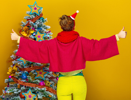 Festive season. Seen from behind stylish woman in colorful clothes near Christmas tree on yellow background showing thumbs up Stock Photo