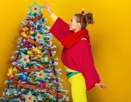 축제의 계절. 유행 여자가 화려한 옷을 입고 크리스마스 트리 근처에 노란색 배경 장식 웃고