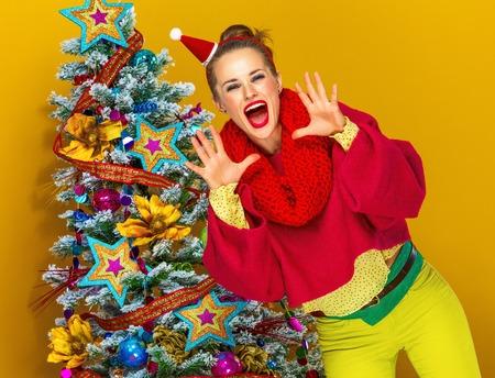 축제의 계절. 화려한 옷을 입은 유행 여자가 크리스마스 트리 근처의 노란색 배경에 웃고 확성기 모양의 손을 통해 소리