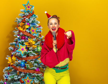 Festive season. smiling young woman in colorful clothes near Christmas tree on yellow background with microphone singing and pointing at camera Stock Photo