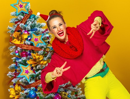 Festive season. smiling trendy woman in colorful clothes near Christmas tree isolated on yellow background showing victory gesture Фото со стока