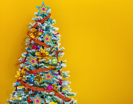 Festive season. colorful Christmas tree isolated on yellow background