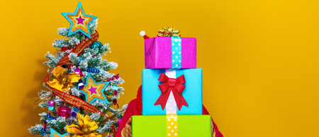 Festive season. stylish woman in colorful clothes near Christmas tree isolated on yellow background holding pile of Christmas present boxes Stock Photo