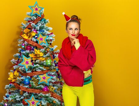 fantasize: Festive season. pensive young woman in colorful clothes near Christmas tree isolated on yellow background Stock Photo