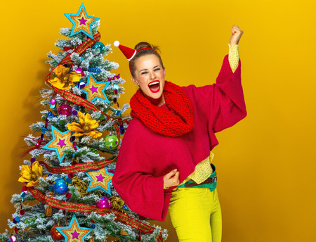 Festive season. smiling trendy woman in colorful clothes near Christmas tree isolated on yellow background rejoicing
