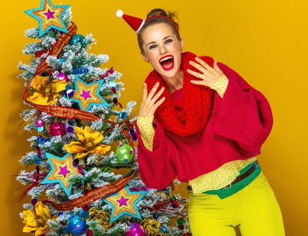 Festive season. excited trendy woman in colorful clothes near Christmas tree isolated on yellow background