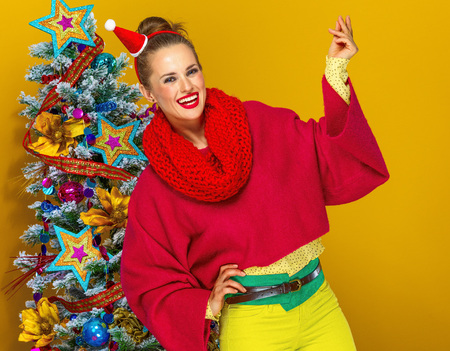 Festive season. happy stylish woman in colorful clothes near Christmas tree on yellow background snapping with fingers