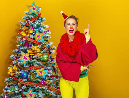 Festive season. smiling trendy woman in colorful clothes near Christmas tree on yellow background having idea Stock Photo